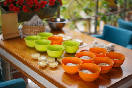 Cookery set of orange and green cups with flour and condensed milk standing at light brown wooden table in cafe with flowers at the background. Shallow dof. Focus at foreground. Stock Photo