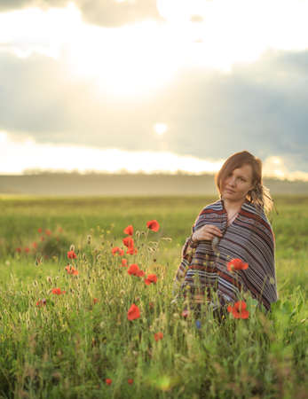 Young beautiful woman in poncho with ethnic pattern sits on field in the middle of green grass and red poppies at the background of cloudy sunset sky and touchs her feather pendant. Stock Photo