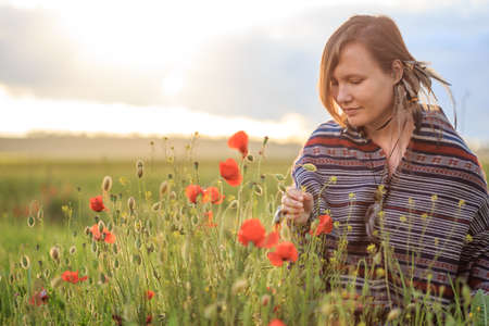 Young beautiful woman in poncho with ethnic pattern and feather decoration sits on field in the middle of green grass and red poppies at the background of cloudy sunset sky and touchs red poppy.