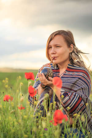 Young beautiful woman in poncho with ethnic pattern sits on field in the middle of green grass and red poppies at the background of cloudy sunset sky and drinks mate from calabash. Stock Photo