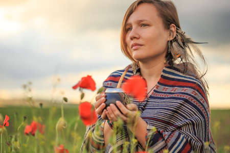 Young beautiful woman in poncho with ethnic pattern sits on field in the middle of green grass and red poppies at the background of cloudy sunset sky and holds calabash with bombilla in hands.