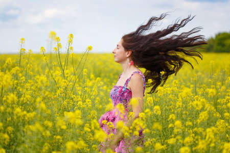 Young beautiful woman with long brown flowing hair in sundress with ethnic flower pattern stands on field of yellow rape flowers with her hair flying in the wind at the background of cloudy sky.