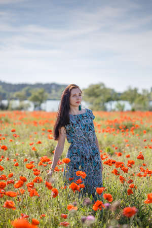 Young beautiful thoughtful woman with long brown hair in sundress with ethnic flower pattern stands on field of green grass and red poppies at the background of cloudy sky, trees and river.