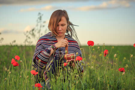 Young beautiful woman in poncho with ethnic pattern sits on field in the middle of green grass and red poppies at the background of cloudy sunset sky and plays tibetan singing bowl.