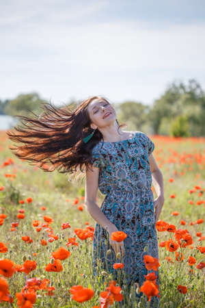 Young happy smiling woman with long brown hair in sundress with ethnic flower pattern stands on field of red poppies at the background of cloudy sky, trees and river with her hair flying in wind. Stock Photo