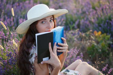 Young beautiful woman with long brown hair in light sundress and hat sits on lavender field with book in her hands and hides her face behind it.