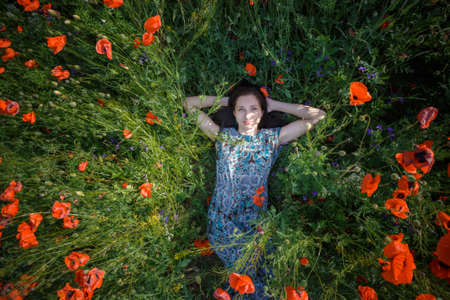 Young beautiful smiling woman in light blue sundress with ornament lies on blooming poppy flower field under summer sunlight with her hands behind head. Stock Photo