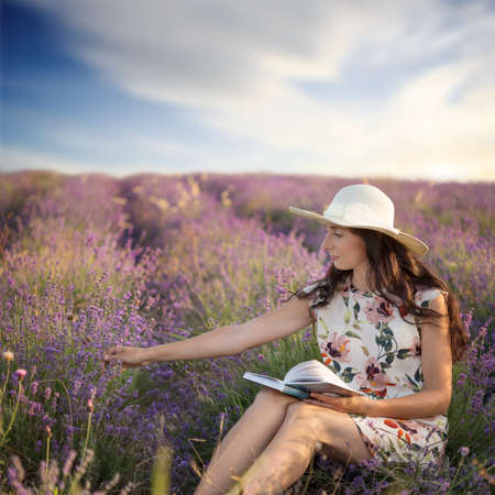 Young beautiful woman with long brown hair in light sundress and hat sits on lavender field with book in her hands and touches flowers.