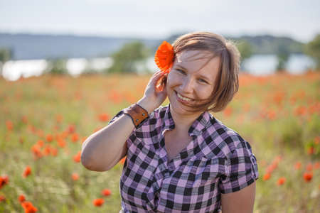 Young beautiful smiling woman in checkered chemise with short blonde hair flying on wind and red poppy in it stands on summer blooming flower field.