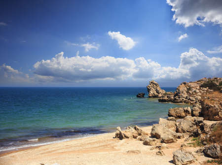Beautiful wild sandy seashore with fancy weathered rocks and cliffs, sunlight, turquoise water and blue cloudy sky above.
