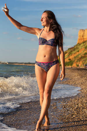 Beautiful smiling slender woman in swimsuit walks along the seacoast in the surf and looks at polished sea glass under sunset light at the background of sand hill. Stock Photo