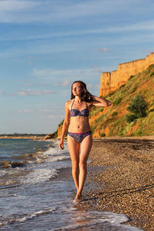 Young beautiful slender woman in swimsuit walks along the seacoast in the surf and touches her hair under sunset light at the background of sand hill.