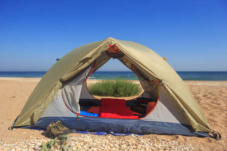 Travel tent with opened door stands at the background of sandy beach, sea, blue sky and green grass, and tracking sneakers standing near