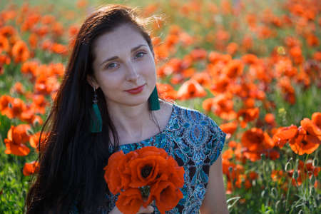 Portrait of young beautiful smiling woman in ornamented ethnic sundress and blue tassel earrings with long brown hair sitting on summer blooming flower field with bunch of poppies. Stock Photo