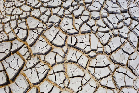 Grunge abstract background of cracked gray dry volcano mud layer with big and deep clefts.