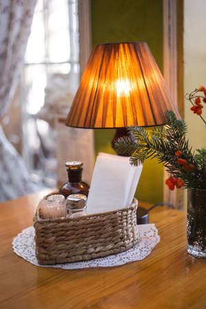 Lamp with orange lampshade stands on wooden polished table with dried plants decoration and wicker basket at the background of window with light patterned curtain.