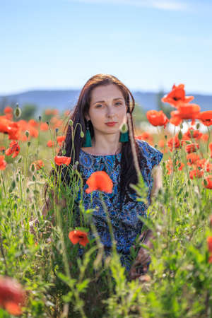 Portrait of young pensive woman in ornamented ethnic sundress and blue tassel earrings with long brown hair sitting on summer blooming flower field with bunch of poppies.