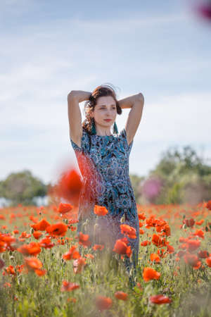 Young beautiful pensive woman in ornamented ethnic sundress and blue tassel earrings with long brown hair stands on summer blooming flower field with her hands behind head.