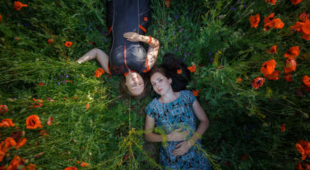 Young beautiful smiling women in ornamented ethnic sundress and silver gray tunic lay on summer blooming poppy flower field. Top view. 版權商用圖片