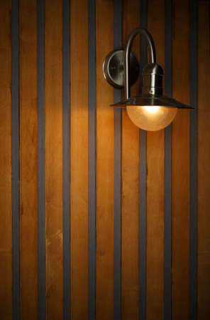 Original minimalist interior with stylish lamp and splash of light on the wall decorated with stripes of vertical wooden panels.