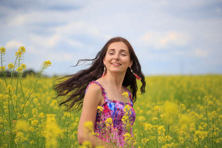 Young smiling woman with long brown flowing hair in sundress with ethnic flower pattern stands on field of yellow rape flowers with her hair flying in the wind at the background of cloudy sky.