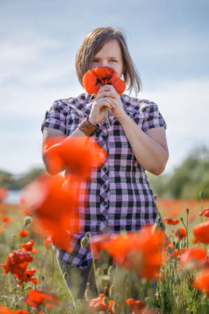 Young beautiful woman in checkered chemise with short blonde hair stands on summer blooming flower field and sniffs bunch of poppies.