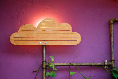 Original interior with wooden cloud and sun lamp decoration, pipes with artificial plants on it at the background of purple colored wall. Stock Photo