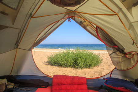 Travel tent with opened door stands at the background of sandy beach, sea, blue sky and green grass. View from within.