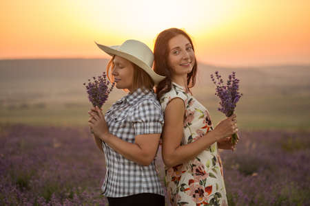 Two happy women in light ornamented dress, checkered chemise and hat stand back to back on blooming lavender field at the background of mountains and sunset with bunches in hands.
