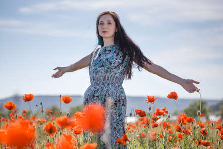 Young beautiful pensive woman with long brown flowing hair in sundress with ethnic flower pattern stands with open arms on field of red poppies at the background of cloudy sky.
