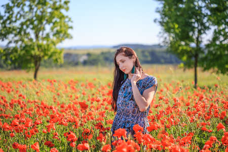 Beautiful thoughtful woman with long brown hair in sundress with ethnic flower pattern and tassel earrings stands on red poppy field and touches her hair.