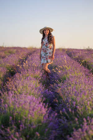 Young happy smiling romantic woman in light patterned sundress and hat stands on lavender field under sunset light.