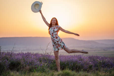 Happy beautiful smiling woman in light ornamented sundress jumps on one leg with her hat in hand on blooming lavender flower field at the background of mountains and sunset. Stock Photo