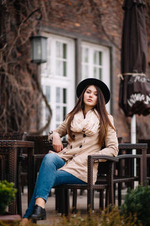 Street fashion concept. Vintage portrait of young woman in spring coat and hat. Flattering hair.