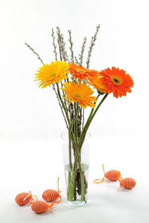 A nice, yellow and orange coloured easter bouquet with marguarites, catkins and easter eggs  photo