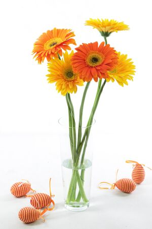 A nice, yellow and orange coloured easter bouquet of marquerites with easter eggs  photo