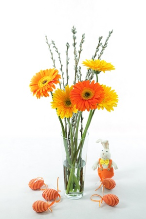 A nice, yellow and orange coloured easter bouquet with easter eggs and rabbit  photo