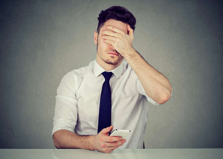 Young formal man using phone and covering face because of doing mistake while working