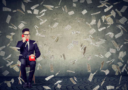 Successful young business man talking on the phone under money rain  Stockfoto
