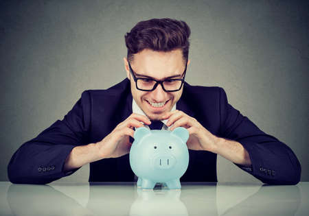 Young formal man in glasses extremely fascinated with money saving in piggy bank.