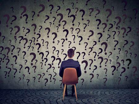 Der junge Geschäftsmann, der auf einem Stuhl vor einer Wand sitzt, hat viele Fragen und wundert sich, was als Nächstes zu tun ist Standard-Bild