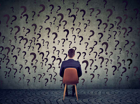 Young business man sitting on a chair in front of a wall has many questions, wondering what to do next