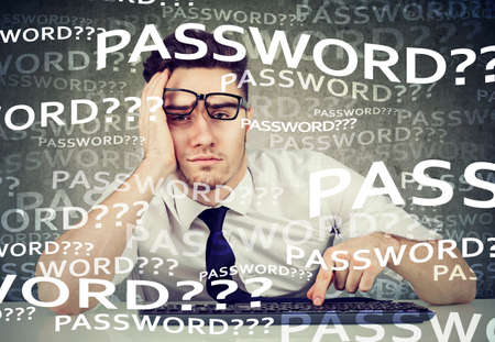 Desperate young business man trying to log into his computer forgot password