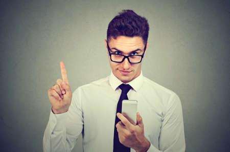 Business man with smartphone showing no, attention with finger hand gesture. Blocking dangerous adult contents. Parental control concept Foto de archivo