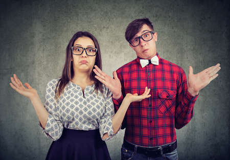 Young stylish couple in glasses looking clueless and shrugging with shoulders looking at camera. Archivio Fotografico