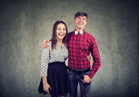 Cheerful young woman and man embracing one another, looking and smiling at camera. Happy couple spending nice time togtether, posing on wall background