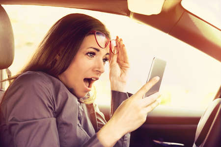 young woman distracted reading a message on cellphone, amazed, while driving a car Imagens