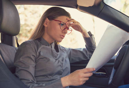 Side view of young woman in eyeglasses sitting in car on driver seat and exploring fine paper looking worried.