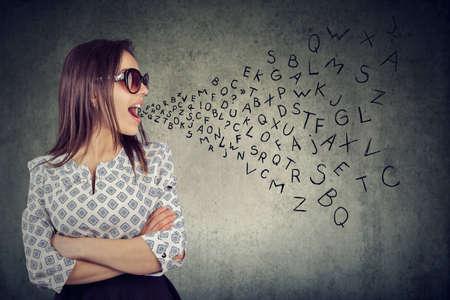 Kobieta w okularach przeciwsłonecznych rozmawiająca z literami alfabetu wychodzącymi z jej ust. Komunikacja, informacja, koncepcja