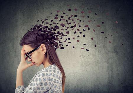 Pérdida de memoria debido a demencia o daño cerebral. Mujer joven que pierde partes de la cabeza como símbolo de una función mental disminuida.
